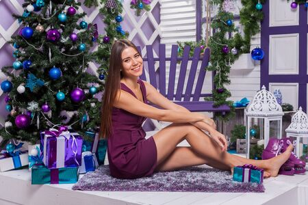 miracle tree: leggy brunette in a turquoise dress sitting on a purple swing on the terrace surrounded by a Christmas tree with baubles and gifts smiling and looking at the camera. Stock Photo