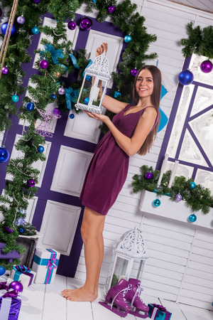 merrymaking: Pretty brunette in a turquoise dress on the white terrace with gifts in his hands next to a Christmas tree and Christmas balls.
