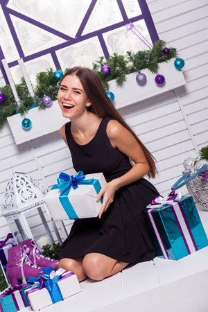 merrymaking: Pretty brunette in a black dress on a white terrace with gifts in his hands next to a Christmas tree with gifts and Christmas balls. Stock Photo