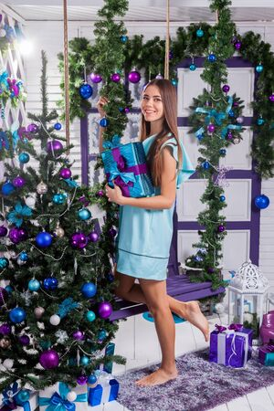 merrymaking: brunette in a turquoise dress standing next to a Christmas tree decorated with purple and blue balloons and holding a gift. Stock Photo