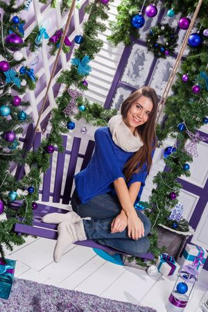 merrymaking: charming brunette in jeans and a blue sweater sits on a swing on white terrace surrounded by Christmas toys, balls and fir trees. Stock Photo