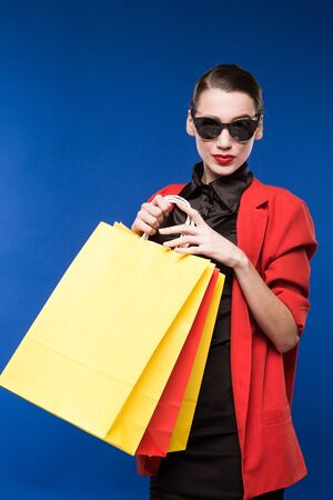 young woman in a jacket and with packages on a blue background Stock Photo