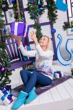 botas de navidad: beautiful young blonde in white sweater and blue jeans sitting on the terrace, surrounded by white Christmas tree with balls and Christmas gifts.