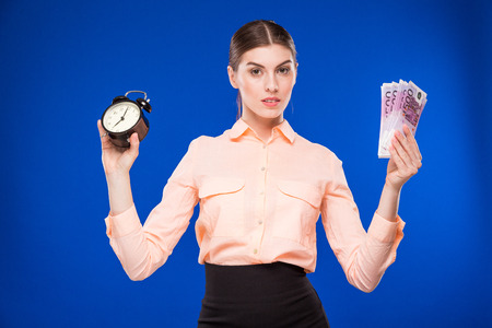 young girl with an alarm clock and money in hands on a blue background Stock Photo