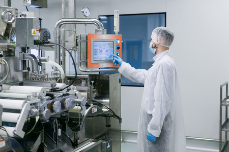 factory worker in white suit is checking readings