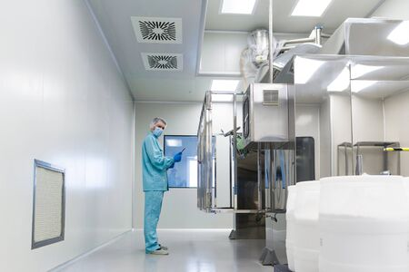 caucasian scientist in blue lab uniform make notes about big steel machine with control panel, white barrels on front, clean room, look at camera Stock Photo