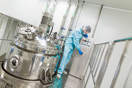 scientist in blue lab suit check control panel near big chromed tanks