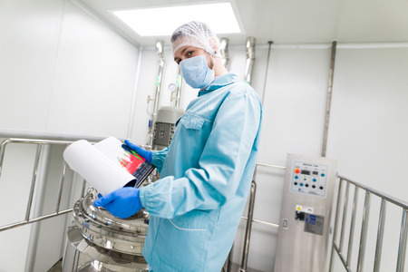 check room: scientist in blue laboratory suit and gas mask stand in clean room and check graphs in tablet