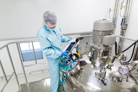 check room: scientist in blue laboratory suit and gas mask stand in clean room and check graphs in tablet near big steel tank