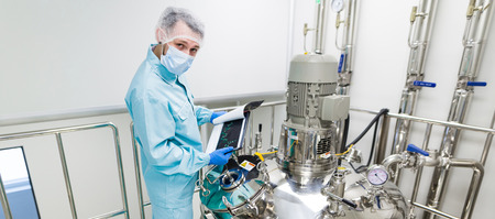 check room: widescreen picture, scientist in blue laboratory suit and gas mask stand in clean room and check graphs in tablet near big steel tank