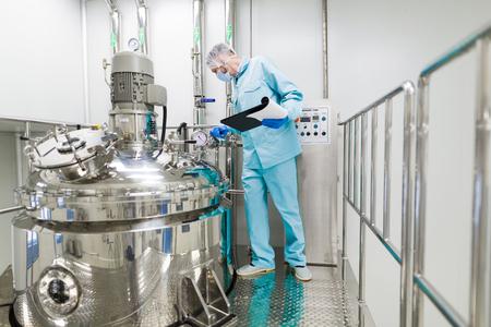 wetenschapper in blauw lab pak werken met het bedieningspaneel, kijk naar de camera