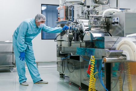 shafts: bended caucasian scientist in blue lab suit trying to fix manufacture machine with shafts