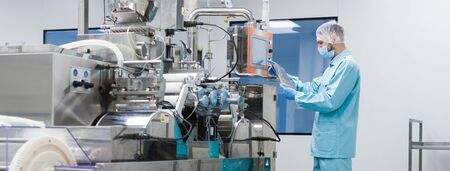 shafts: widescreen picture, caucasian scientist in blue lab suit trying to fix manufacture machine with shafts in clean factory
