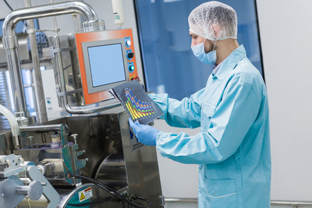 caucasian scientist in blue lab uniform work with manufacture machine with shafts and control panel