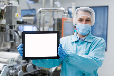 shafts: blured background, caucasian scientist man in blue lab uniform stand near manufacture machine with shafts, show empty tablet, close picture, focus on tablet Stock Photo