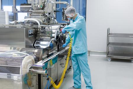 shafts: caucasian scientist in blue lab uniform configure manufacture machine with shafts and control panel