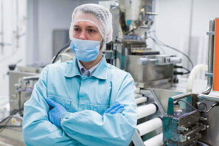 shafts: caucasian scientist in blue lab uniform stand near machine with shafts, stand with crossed hands Stock Photo