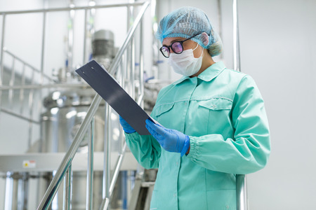scientist in blue lab uniform stand on chromed stairs and look in tablet, steel tank on background