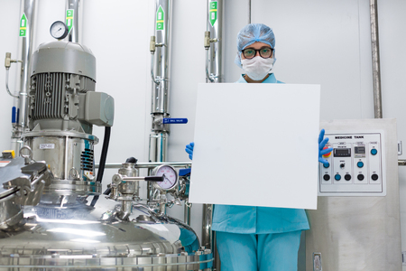 chrome man: caucasian scientist in blue lab uniform stand near compressor engine and hold empty paper towards camera Stock Photo