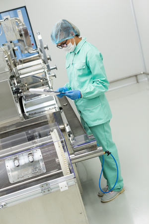 chrome man: vertical picture, caucasian factory worker in blue lab suit fixes manufacture machine