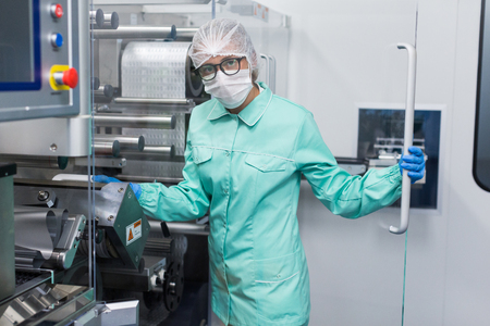 shafts: caucasian factory worker in blue lab suit work with machine, stand behind glass panel, look at camera Stock Photo