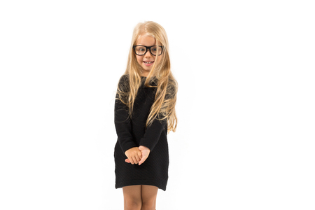 Isolated on white, pretty caucasian blonde little girl in black dress, glasses, black socks and white shoes standing, look at camera, shy