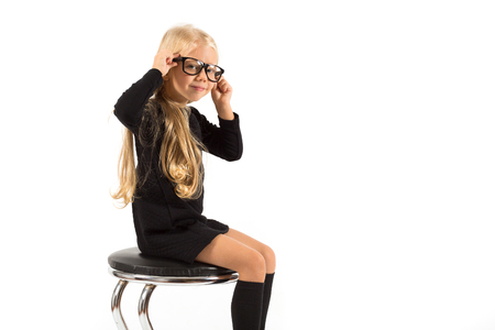 Isolated on white, pretty caucasian blonde little girl in black dress, glasses, black socks and white shoes sitting, hands on the head