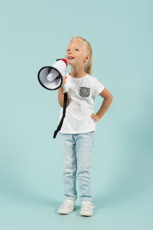 loudspeaker: Vertical picture, isolated on blue, pretty caucasian blonde little girl in white t-shirt, light blue trousers and white shoes stands and holds a megaphone