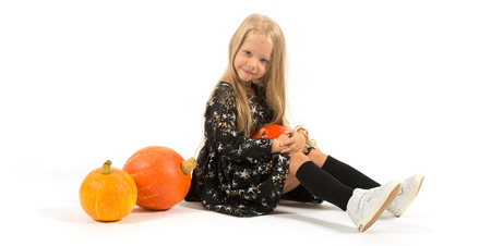 Widescreen picture, isolated on white, pretty caucasian blonde little girl in black dress with stars, black socks and white shoes sitting near the pumpkins, hold one in hands Фото со стока
