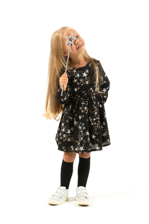 Vertical picture, isolated on white, beautiful caucasian blonde little girl in black dress with stars, black socks and white shoes holds magic wand look up through the wand Stock Photo