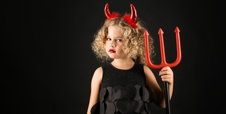 Widescreen picture, isolated on black adorable caucasian little girl in black dress, with red horns on head hold trident