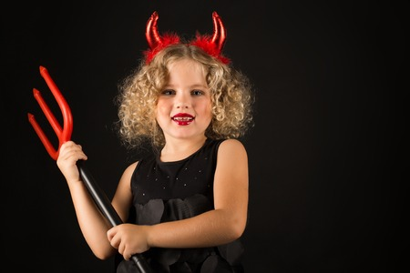 Isolated on black, beautiful caucasian blonde little girl in black dress, with red horns on head hold trident both hands, look at camera
