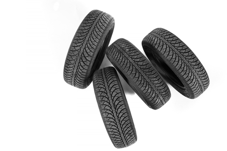 pneumatic tyres: Isolated on white, four new black rubber automobile tires with protector standing, from top Stock Photo
