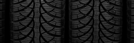 grooves: Wide-screen closeup picture, two black rubber automobile tire with protector