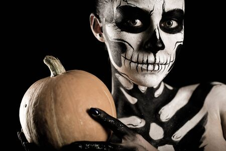Isolated on black, closeup picture, young brunette caucasian pretty woman with scull body art with a pumpkin in hands, grey eyes, look at camera