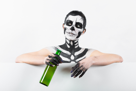 Isolated on white, closeup picture, young brunette caucasian pretty woman with scull body art holds green beer bottle, grey eyes