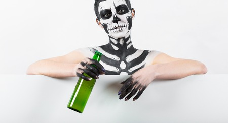 Isolated on white, closeup picture, young brunette caucasian pretty woman with scull body art holds green beer bottle, grey eyes, look at camera