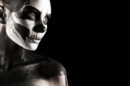 Isolated on black, closeup picture, beautiful young blonde caucasian woman with scull body art, grey eyes, position at left, look at right