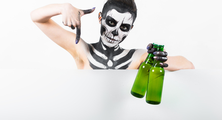 Isolated on white, closeup picture, young brunette caucasian pretty woman with scull body art holds green beer bottle, grey eyes, points down at the copy space