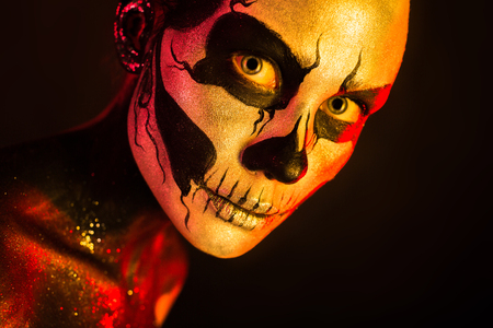 Isolated on black, closeup picture, toned red and yellow, beautiful  creepy young blonde caucasian woman with scull body art, grey eyes, look at camera