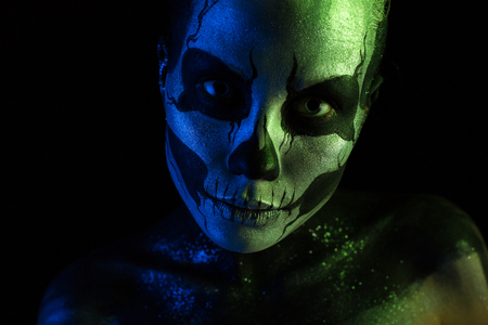 Isolated on black, closeup picture, toned green and blue, beautiful  creepy young blonde caucasian woman with scull body art, grey eyes Stock Photo