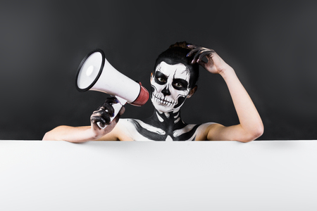 Isolated on black, closeup picture, young brunette caucasian pretty woman with scull body art holds megaphone, grey eyes