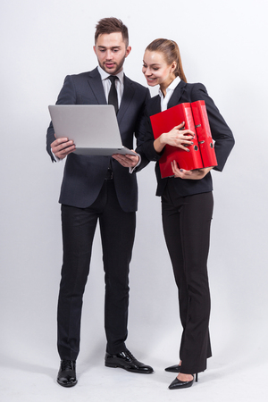 Couple of attractive young caucasian businesswoman with ponytail in black suit with folders in hands and businessman in black suit with laptop Isolated on grey, vertical picutre Stock Photo