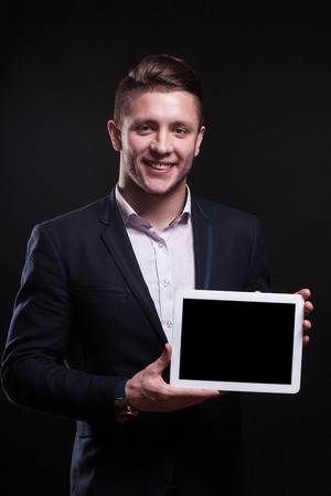 Adult attractive brunette caucasian businessman in black suit and costly watch stand and hold empty tablet, smiling Isolated on black, vertical picture