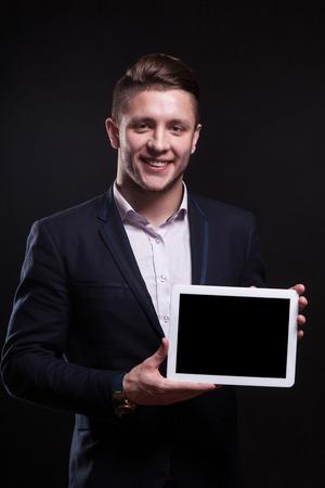 Volwassen aantrekkelijke donkerbruine Kaukasische zakenman in zwart kostuum en duur horloge tribune en greep lege tablet, glimlachen geïsoleerd op zwart, verticaal beeld Stockfoto