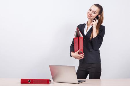 어린 소녀 관리자는 노트북과 테이블 옆에 흰색 배경에 빨간색 폴더 사무실을 누른 전화 얘기. 스톡 콘텐츠