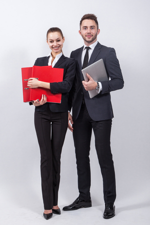 two modern businessman standing on a white background with a laptop and office folders red, man and woman in business suits.