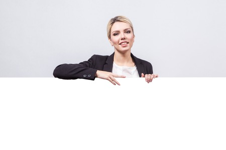 studio portrait on white background successful business woman in a business suit with a board for a number of advertising which could be your text.