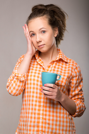 a young housewife in an orange shirt with a cup of coffee in hand on gray background Stock Photo