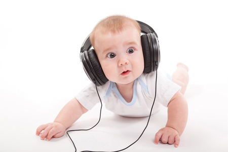 charming baby on a white background with headphones listening to music. Photo from the depth of focus and artistic blur Stock Photo